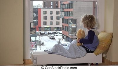 Girl with best friend teddy bear looking at snow fall...