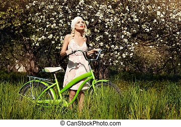 Girl with bicycle in the park.