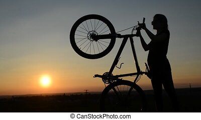 Girl with bicycle in the sunset. - Silhouette of a girl with...