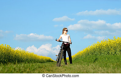 Girl with bicycle on a dirt road in rapeseed field.