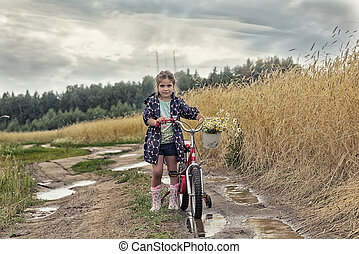 girl with bicycle stand on the rural road in a wheat field with a bouquet of camomiles during a rain