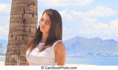 girl with big bust in white smiles by palm trunk on beach -...