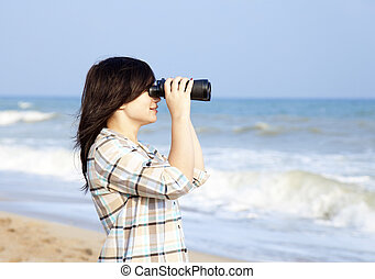 Girl with binocular at the beach.