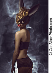 girl with bizarre bunny mask - curly woman posing in Easter...