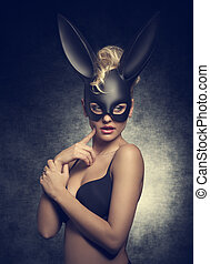 sensual blonde lady with curly hair-style posing like playgirl with black bra and bizarre bunny mask on the face.