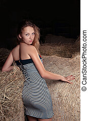 girl with blond hair is in the hayloft - Beautiful young...