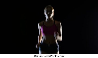 Girl with blond hair running on a black background. Silhouette. Close up