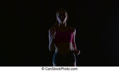 Girl with blond hair running on a black background. Silhouette. Slow motion