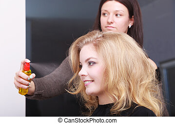 Girl with blond wavy hair by hairdresser. Hairstylist with hairspray and female client. Young woman in hairdressing beauty salon. Hairstyle.