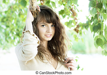 Girl with blue eyes in the foliage