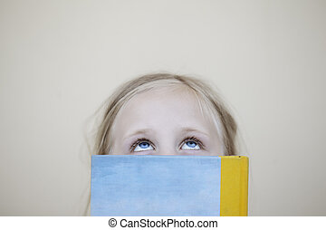 Girl with book looking up
