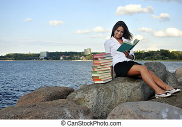 girl with books sitting on a rock by the sea