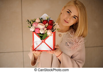 Girl with bouquet in a gift box