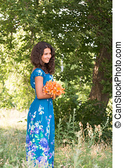 Girl with  bouquet of lilies in the park