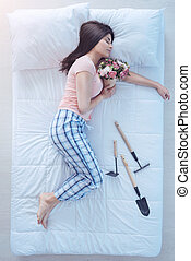 Girl with bouquet taking nap after working in garden