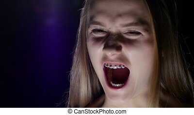 Girl with braces is very angry. Blue