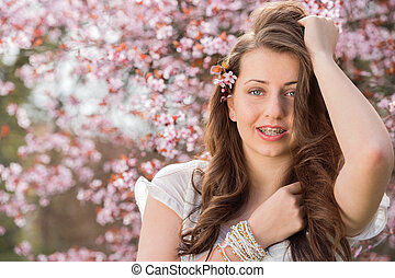 Girl with braces posing near blossoming tree