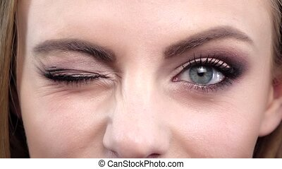 Girl with bright makeup winking into the camera. Close up. Slow motion