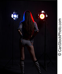 girl with bright studio flashes and flare on background from behind