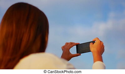 girl with brown hair photographing a beautiful landscape on the phone