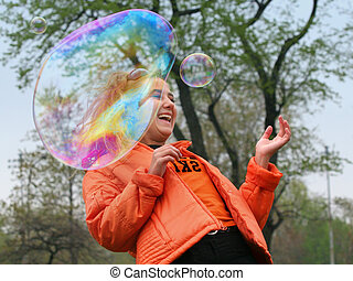 Girl with bubbles - Girl playing with bubbles in a park