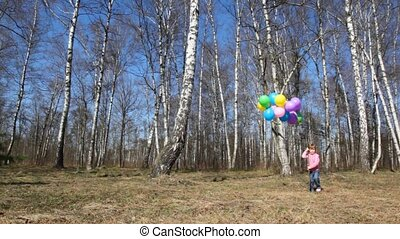 girl with bunch of balloons walks in forest - little girl...