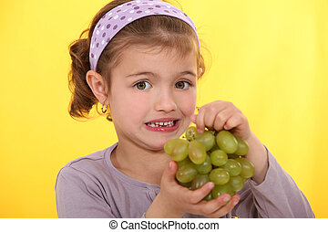 Girl with bunch of grapes