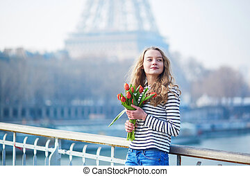 Girl with bunch of red tulips near the Eiffel tower