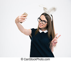 Girl with bunny ears making selfie photo on smartphone