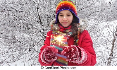 Girl with burning sparlkes on winter forest