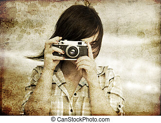 Girl with camera at the sea.