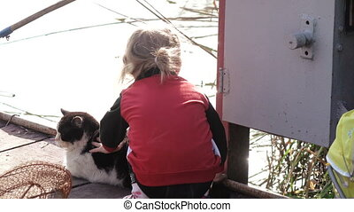 Girl with cat fishing - On wooden pier granddaughter and...