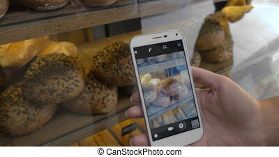 Girl with cellphone taking pictures of bread in the bakery