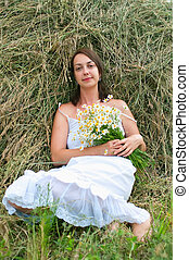 girl with chamomiles on haystack