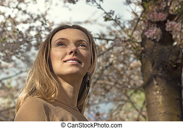 Girl with Cherry Blossom. Beautiful Blonde Young Woman with Saku