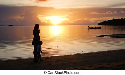 Girl with children go on walks and play on the beach during sunset