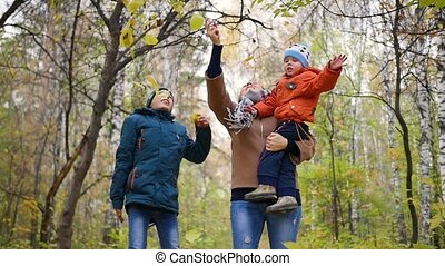 Girl with children in autumn Park throws yellow leaves. Laughing and smiling happy family