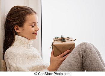 girl with christmas gift sitting at home - childhood,...