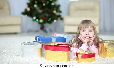 Girl with christmas gifts lying