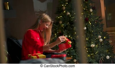 Girl with Christmas hat makes wishes and opens a Christmas gift package.concept of holidays and new year.the girl is happy and smiles with christmas gift in hand.