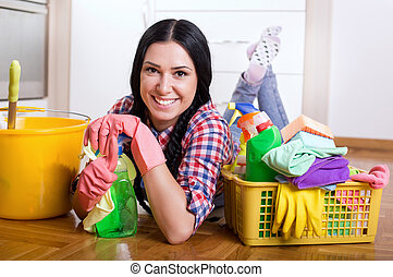 Girl with cleaning supplies on kitchen floor