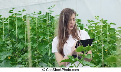 Girl with clipboard takes notes and considers rows of plants