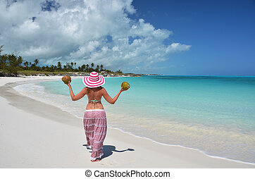 Girl with coconuts at a beach of Little Exuma, Bahamas