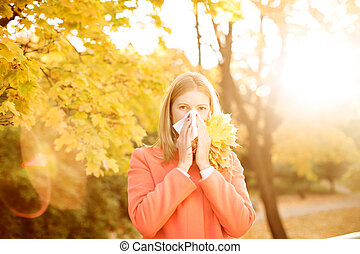 Girl with cold rhinitis on autumn background. Fall flu ...