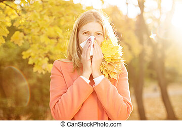 Girl with cold rhinitis on autumn background