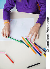 Girl With Color Pencils And Paper At Desk