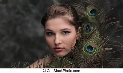 girl with colored makeup and peacock feather