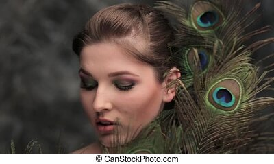 girl with colored makeup and peacock feather - Beautiful...