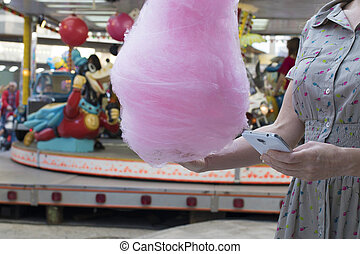 girl with cotton candy in amusement park