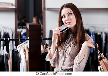 Girl with credit card is in the shopping mall